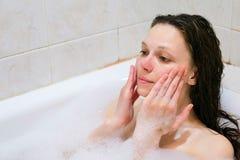 清洗她的面孔的美丽的妇女与在白色浴的泡沫治疗 免版税库存照片