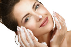 清洗她的面孔的美丽的妇女与泡沫治疗 库存照片