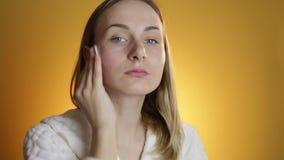 清洗她的面孔,在黄色背景的年轻可爱的妇女 股票录像