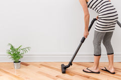 清洗屋子的妇女真空 免版税库存图片