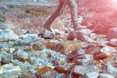 清洗山小河,并且横渡它的远足者定了调子和晴朗 库存照片
