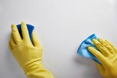 清洁工的手有旧布和去壳机工作的 免版税库存图片