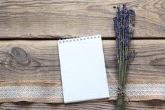清洗开放笔记本与淡紫色在土气木头的花花束 免版税库存图片