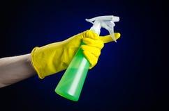 清洗房子和擦净剂题材:在拿着清洗的一副黄色手套的人的手一个绿色浪花瓶在一深蓝backgr 免版税库存照片