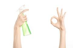 清洗房子和擦净剂题材:拿着清洗的人的手一个绿色浪花瓶被隔绝在白色背景 免版税库存图片