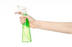 清洗房子和擦净剂题材:拿着清洗的人的手一个绿色浪花瓶被隔绝在白色背景 免版税库存照片