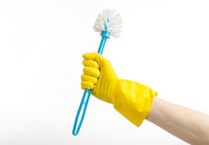 清洗房子和清洗洗手间:拿着在黄色防护手套的人的手一把蓝色洗手间刷子隔绝在白色 免版税库存图片