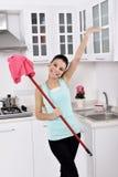 清洗房子的微笑的女孩 免版税库存图片