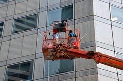 清洁摩天大楼窗口和墙壁从废气管平台 库存图片