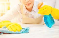 清洗桌的黄色手套的主妇 免版税库存照片