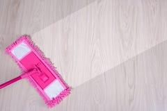 清洁概念-桃红色弄湿清洗木地板的拖把 免版税库存照片