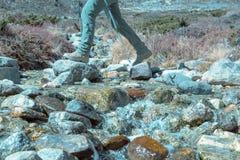 清洗横渡它的山小河和远足者被定调子的时髦 免版税库存照片