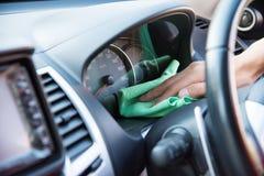 清洗汽车内部与绿色microfiber布料 免版税库存照片