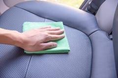 清洗汽车内部与绿色microfiber布料 免版税图库摄影