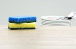 清洁海绵和盘在厨房里 图库摄影