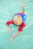 男孩清洁游泳池 免版税库存照片