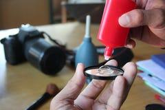 清洗照相机的摄象机镜头擦净剂和手 库存图片