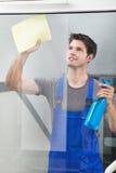 清洗玻璃的擦净剂与纸 免版税库存照片