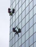 清洗玻璃门面旅馆的卫生工作者 图库摄影