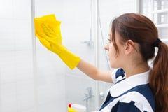 清洗玻璃阵雨小卧室的管家 库存照片