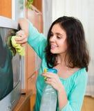 清洗电视的深色的妇女 免版税库存照片
