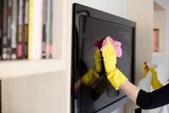 清洗电视的黄色橡胶手套的妇女 免版税库存照片