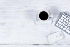 清洗白色桌面与简单的计算机外围和咖啡 免版税库存图片