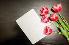 清洗白色纸片和桃红色郁金香在黑木背景 顶视图,文本的空间 图库摄影