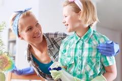 清洗他们的房子的母亲和女儿 库存图片