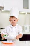 清洗他的板材的小男孩厨师,当烹调时 免版税库存图片