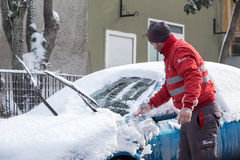 清洗他的汽车的人从雪 图库摄影