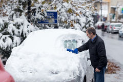 清洗他的汽车的人从雪 免版税图库摄影
