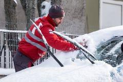 清洗他的汽车的人从雪 库存图片