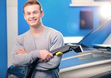 清洗他的汽车的英俊的人 库存照片