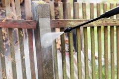 清洗的肮脏的庭院操刀有高压洗衣机的岗位 库存照片