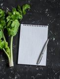 清洗空白的笔记薄和新鲜的芹菜分支  饮食、计划和健康生活方式的概念 免版税图库摄影