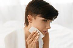 清洗美丽的新鲜的皮肤的秀丽妇女与引人入胜的组织 免版税库存照片