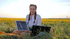 清洁能源,少妇谈话在膝上型计算机使用太阳电池板户外,女性在与笔记本充电器的背后照明从 股票录像