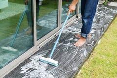 清洗黑花岗岩地板的泰国人与刷子和化学制品 库存图片