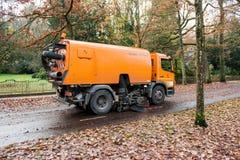 清洗街道的橙色道路清扫工机器 免版税库存照片