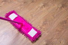 清洗镶花地板与桃红色拖把 免版税库存照片