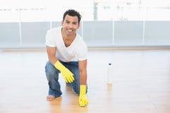 清洗镶花地板的微笑的人在房子 库存图片
