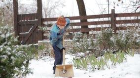 清洁雪在房子附近的冬天 孩子清洗铁锹积雪的轨道 影视素材