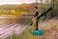渔冒险,鲤鱼渔 湖岸的渔夫与伪装捕鱼装置 图库摄影