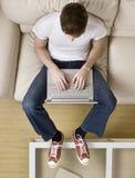渔冷静高膝上型计算机人键入的查阅年轻人 免版税库存图片