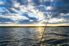 渔在日落期间的路剪影 反对海洋的结尾杆日落的 在盐水小船的钓鱼竿在渔场天期间  免版税库存图片