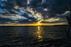 渔在日落期间的路剪影 反对海洋的结尾杆日落的 在盐水小船的钓鱼竿在渔场天期间  免版税库存照片