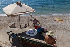 渔夫、抓住和妇女在海滩的读书报纸 免版税库存图片