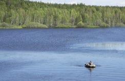 渔夫与一艘橡皮艇的抓住鱼 库存照片
