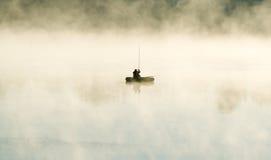 渔夫乘在雾的小船 免版税库存图片